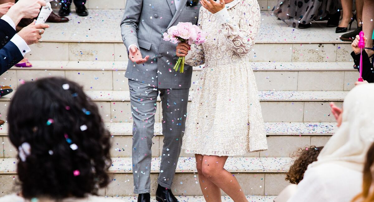 Wedding Loans | just married couple walking down the steps with confetti