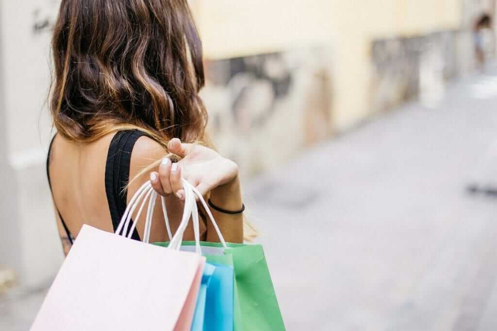 women holding multiple shopping bags after spending cash quickly